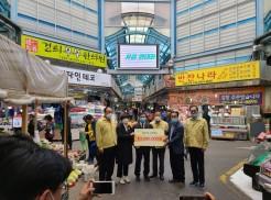 망원동월드컵시장에서 중소기업사랑나눔재단 이사장외 2인과 지원단체장 2인 후원물품 전달판넬을 들고 촬영하고 있는 모습
